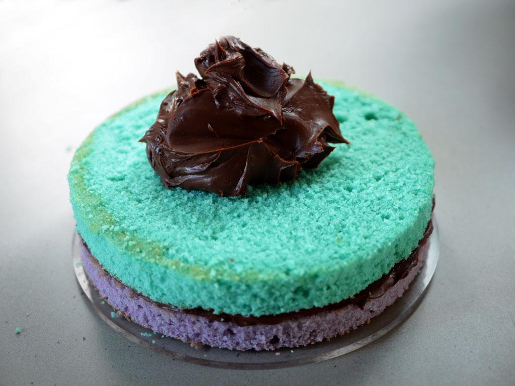 מריחת גנאש שוקולד בין שכבות העוגה